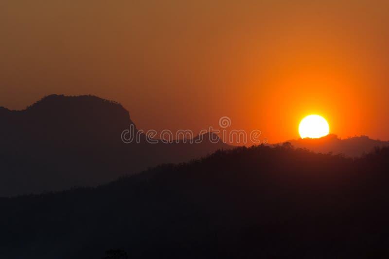 与山剪影的日落日出 免版税库存照片