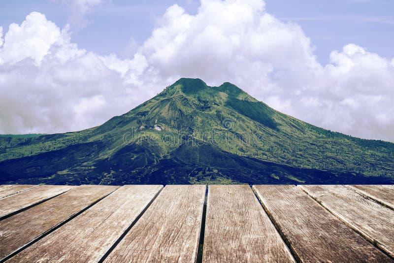 与山和天空,葡萄酒口气风景的木大阳台  免版税库存照片