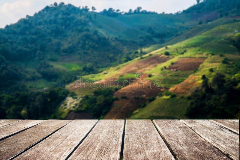 与山和天空,葡萄酒口气风景的木大阳台  免版税库存图片
