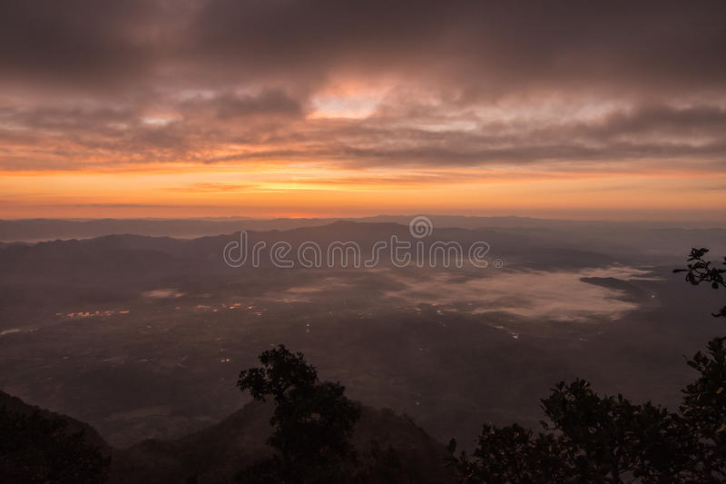与山和海薄雾风景的微明 库存图片