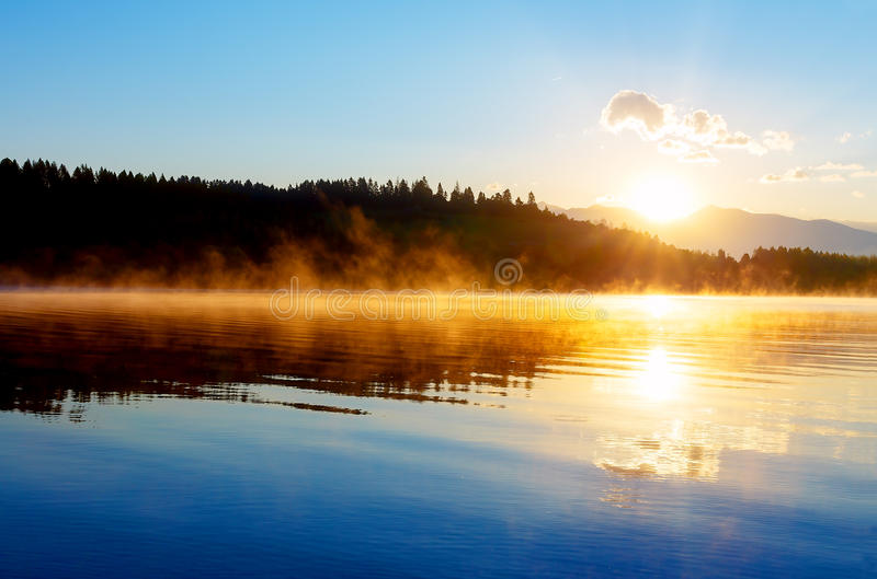 与山和湖的美好的风景在金黄蓝色和橙色口气的黎明 库存图片