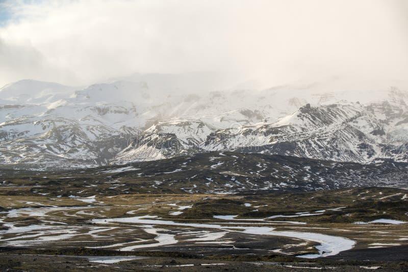 与山和雪暴风云,冰岛的冬天风景 免版税库存照片