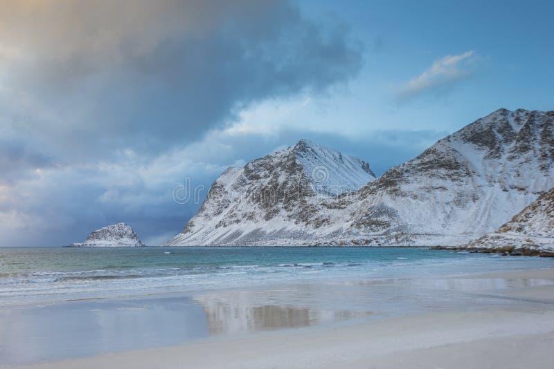 与山在背景中,美好的日落的透明的冬天海滩在挪威 库存照片