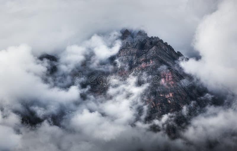 与山的庄严场面在云彩在阴暗晚上 图库摄影