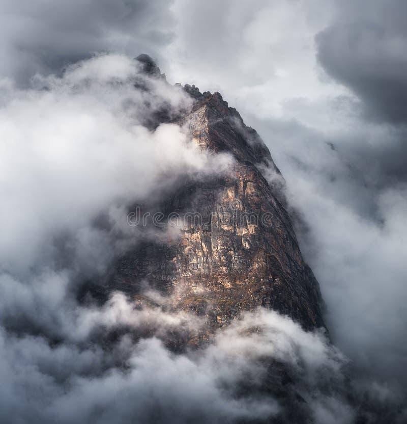 与山的庄严场面在云彩在阴暗晚上 免版税库存图片