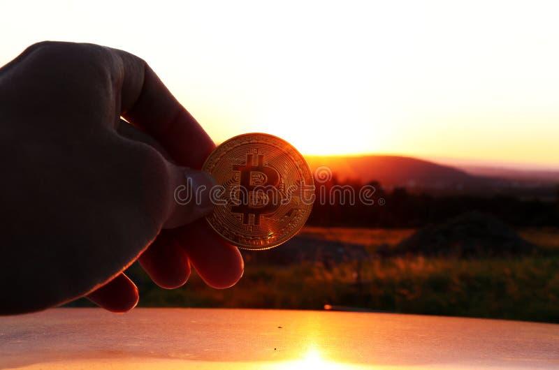与山的美好的日落并且那里是有汽车金黄bitcoin和屋顶的手  库存图片
