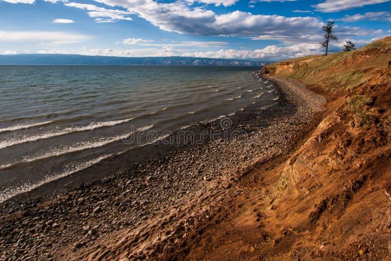 与山的贝加尔湖湖边在背景中和美好的云彩和光 免版税库存图片