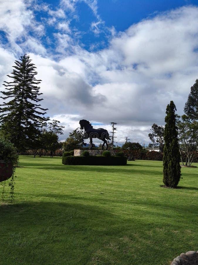 与山的马与蓝天的雕塑和树 免版税库存照片