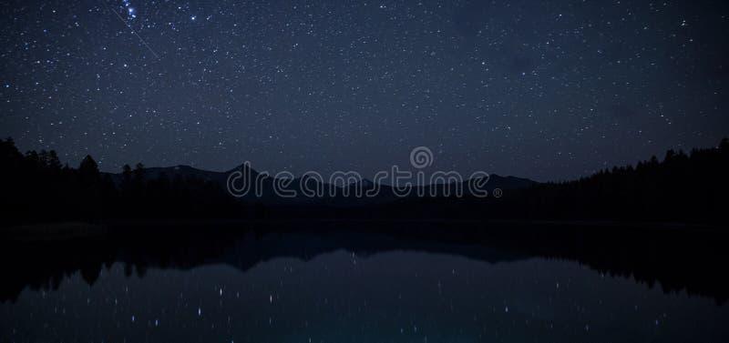 与山脉的Mirror表面湖惊人的风景在与天空的晚上与明亮的星无数  免版税库存图片