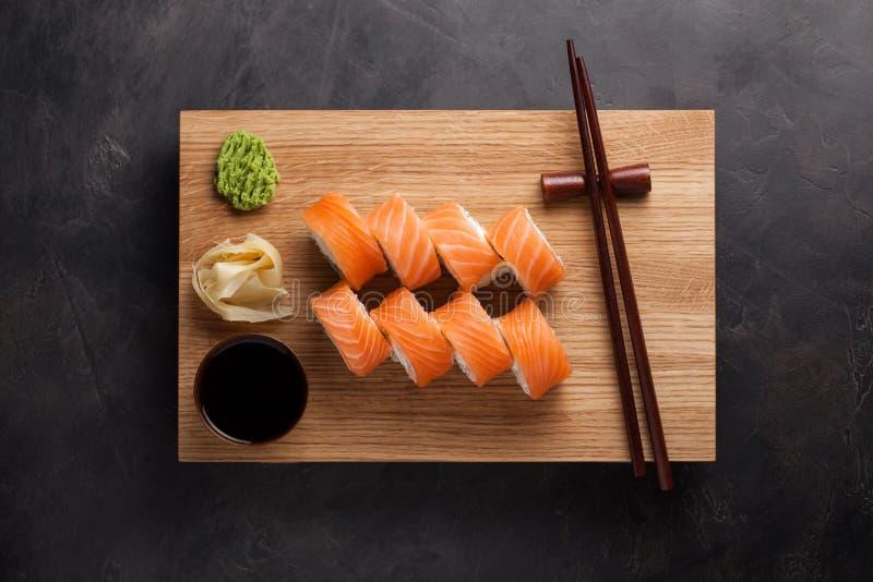 与山葵、姜和酱油的经典费城卷在一个木板 三文鱼,费城乳酪,黄瓜,鲕梨 J 图库摄影