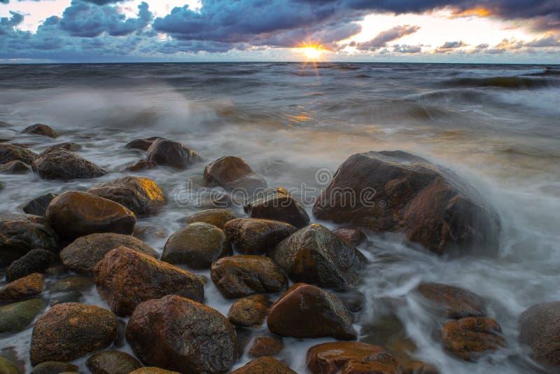 与岩石、风暴和落日的海风景 波浪、岩石、风暴和云彩 n 免版税库存照片