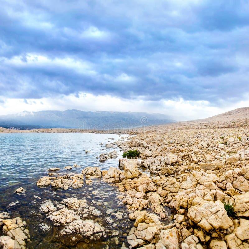 与岩石五颜六色的海岸线和海的平静的全景摄影 库存照片