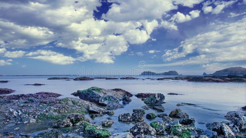 与岩石和剧烈的云彩的平静的海湾 库存照片