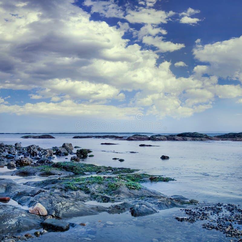 与岩石和剧烈的云彩,大连,中国的海滨 免版税库存照片