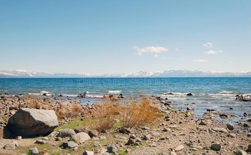 与岩石和雪山的太浩湖岸 免版税库存照片