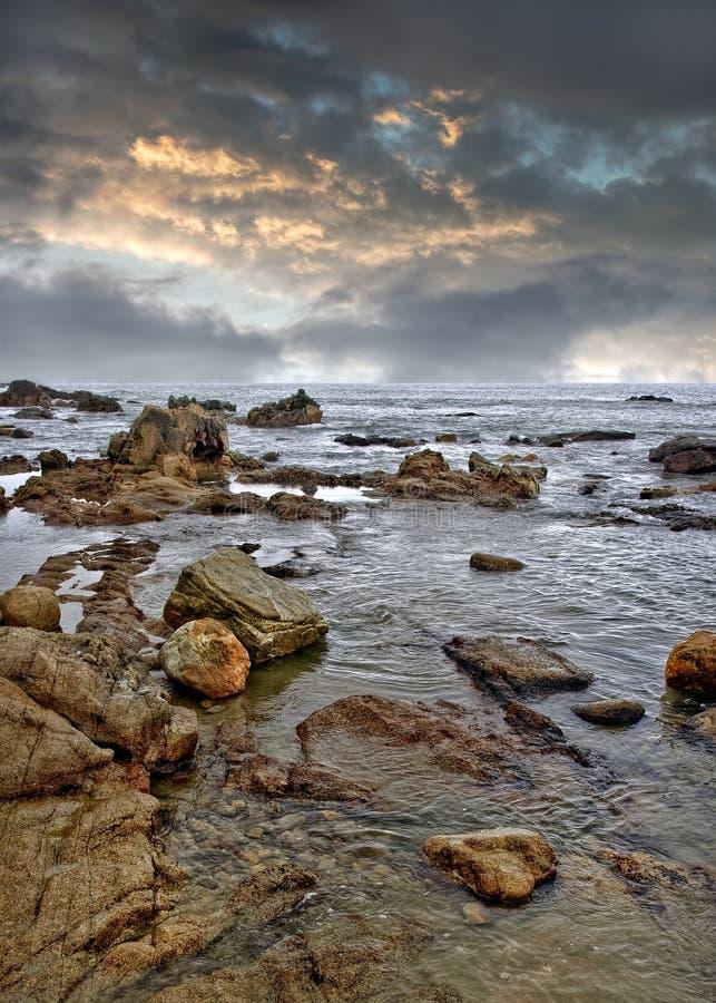 与岩石的平静的海滨在风暴,海南岛,中国之前 免版税库存图片