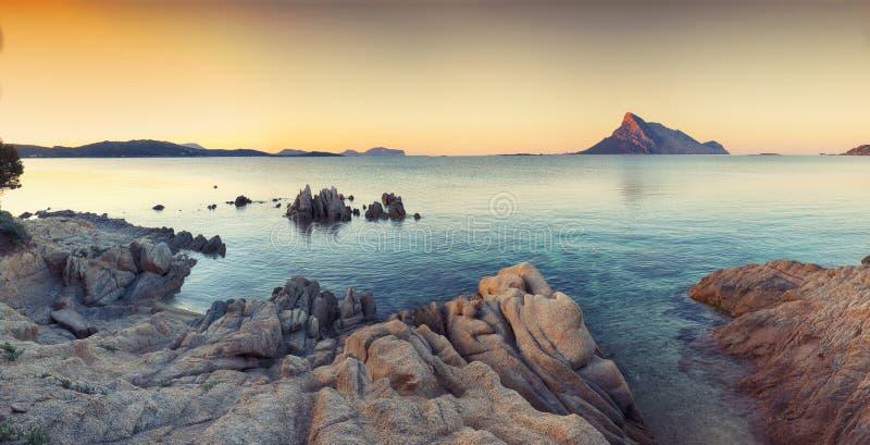 与岩石的意想不到的天蓝色的水在海滩日落的波尔图塔韦尔纳附近 免版税库存照片