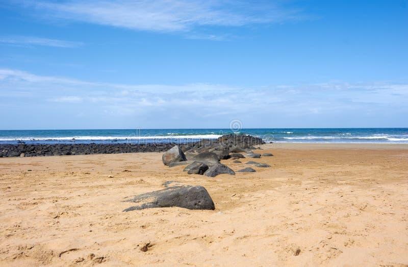 与岩石的沙滩由海浪 图库摄影