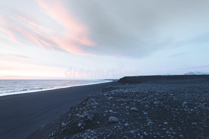 与岩石的海滨和在日落, solheimasandur的多云天空 库存图片