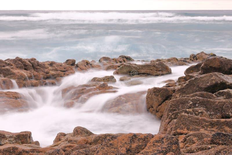 与岩石的长的曝光摄影在与海的海岸有波浪的在夏天 库存照片