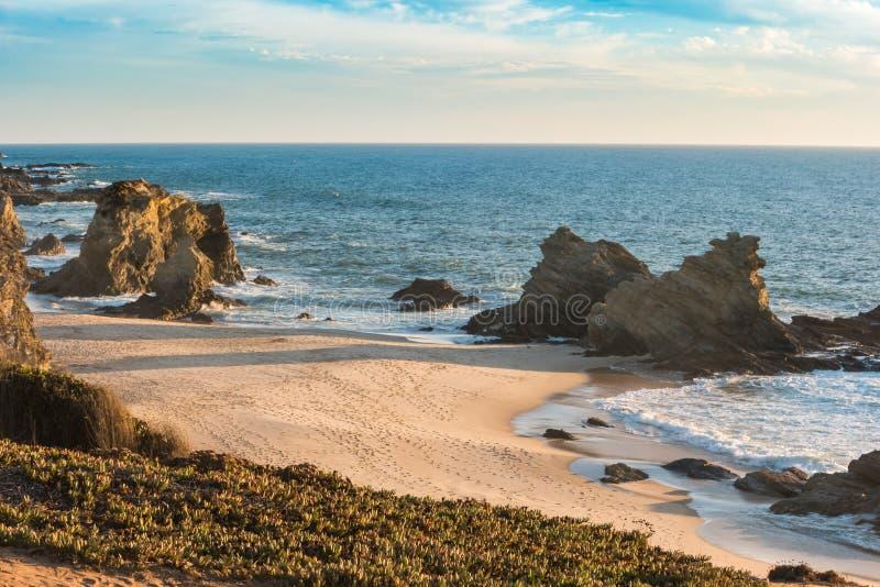 与岩石的Samouqueira海滩在波尔图Covo在阿连特茹,葡萄牙 免版税库存图片