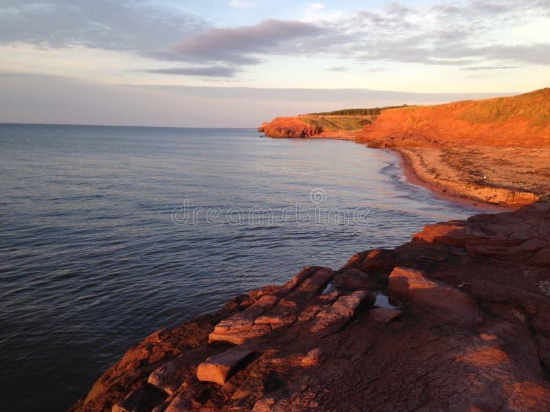 与峭壁的红色沙子海滩在爱德华王子岛 免版税库存照片