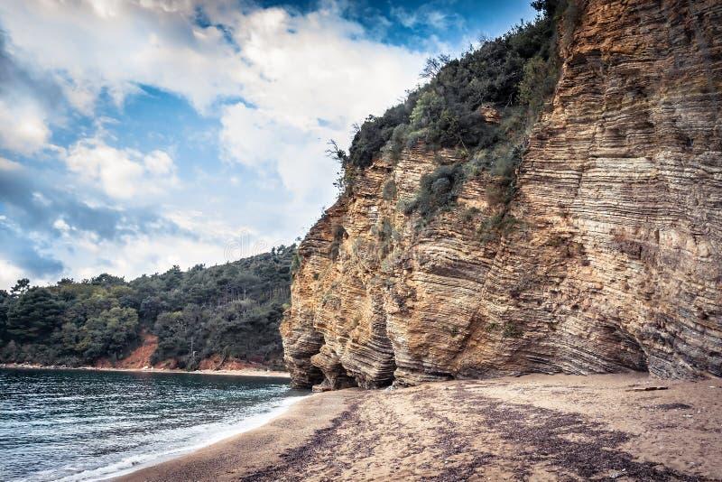 与峭壁的风景海滩和岩石围拢与透明绿松石在黑山海岸线的欧洲国家浇灌在秋天 免版税库存照片