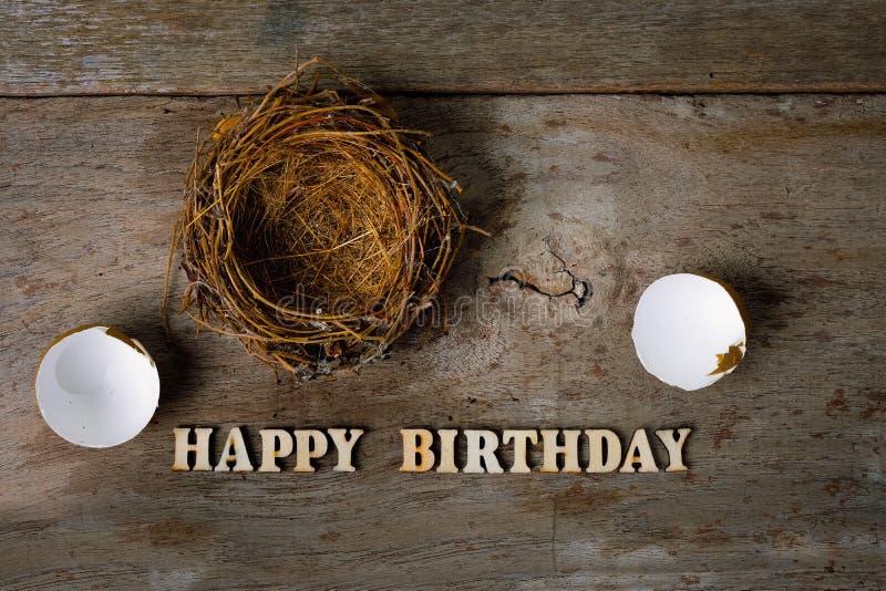 与巢木字母表的被打碎的蛋壳生日快乐概念的 图库摄影