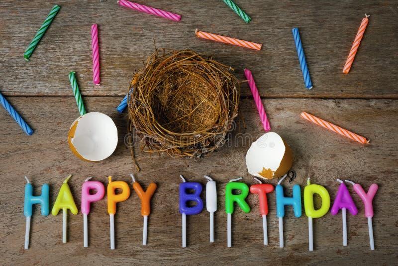 与巢的被打碎的蛋壳和蜡烛为生日快乐Conce 免版税库存照片
