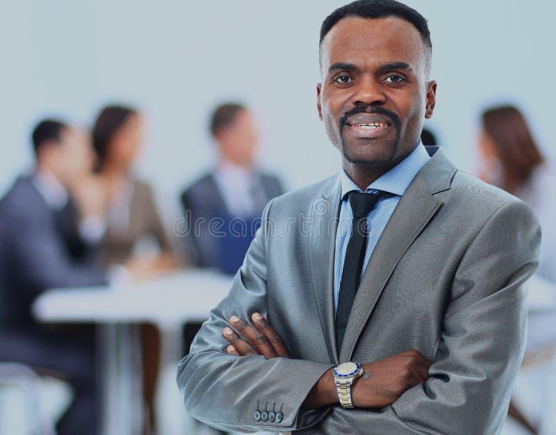 与工作他的队的愉快的非裔美国人的商人后边 免版税库存图片