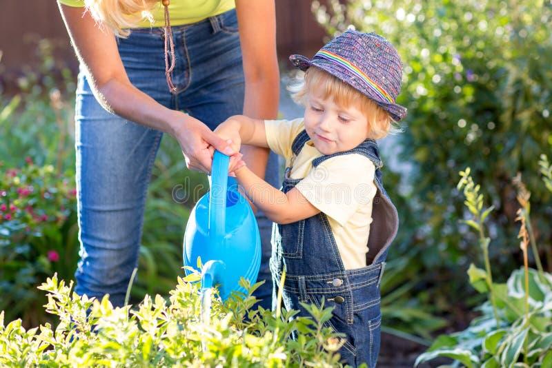 与工作在庭院里的妈妈的孩子 儿童浇灌的花 母亲帮助小儿子 免版税库存照片