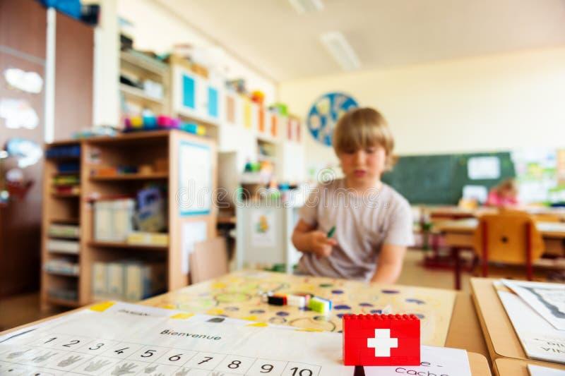 与工作在教室的逗人喜爱的小男孩的背景 免版税库存图片
