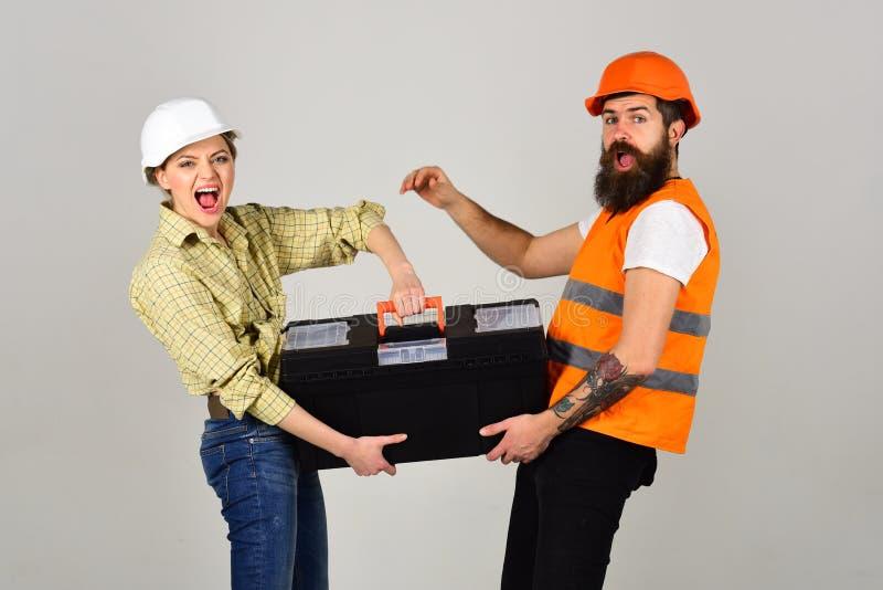 与工具箱,在爱的夫妇的建造者做修理灰色背景 r 激动的盔甲的微笑的妇女 图库摄影