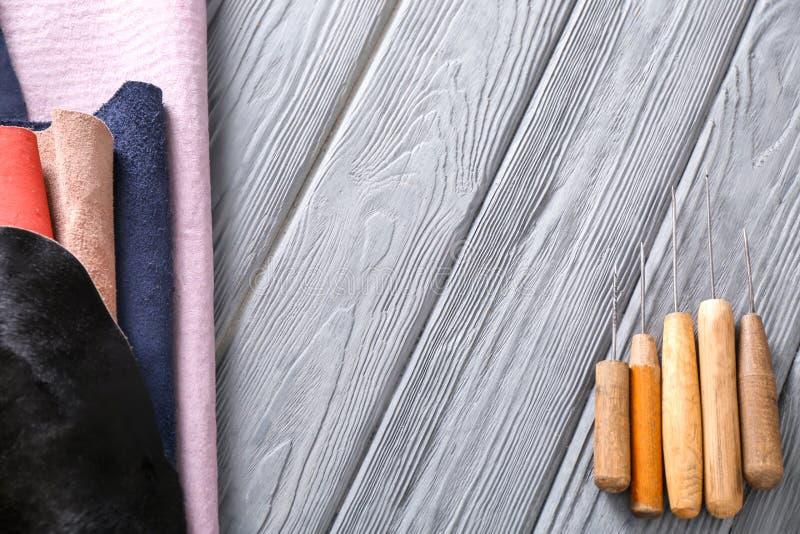 与工艺工具的五颜六色的皮革在木背景 免版税库存图片