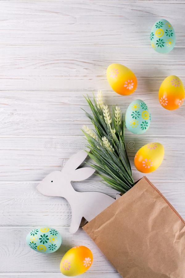 与工艺纸包裹、五颜六色的复活节彩蛋、装饰木兔宝宝和花的复活节构成 平的位置,顶视图, 免版税库存图片