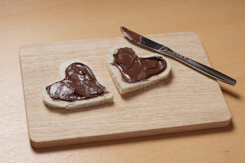 与巧克力传播的心形的多士切片 库存照片