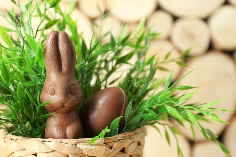 与巧克力复活节兔子的在被弄脏的背景的篮子和鸡蛋 库存图片
