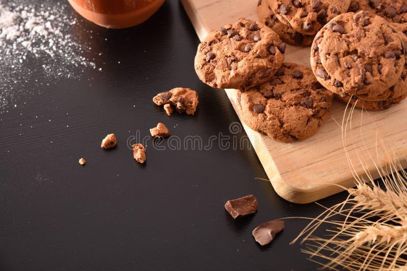 与巧克力片的饼干在黑桌上举起了自创 库存照片