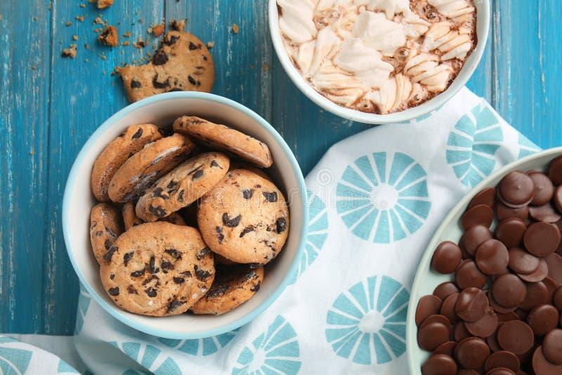 与巧克力片的鲜美曲奇饼在碗和咖啡在颜色木桌上的 库存图片