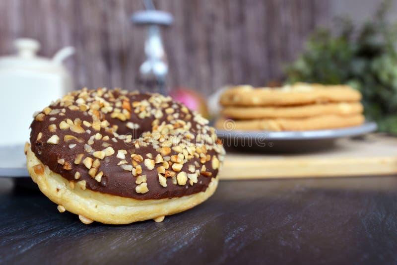 与巧克力给上釉和坚果的鲜美看起来的家庭焙制的多福饼洒 库存图片