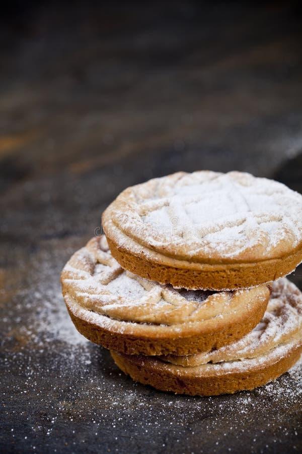 与巧克力装填和糖粉末的新鲜的被烘烤的馅饼在黑背景 免版税库存图片