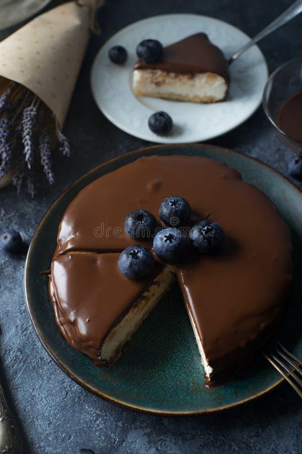 与巧克力顶部和新鲜的有机莓果,在黑暗的石背景的淡紫色的自创蓝莓乳酪蛋糕 有选择性的foc 免版税库存照片