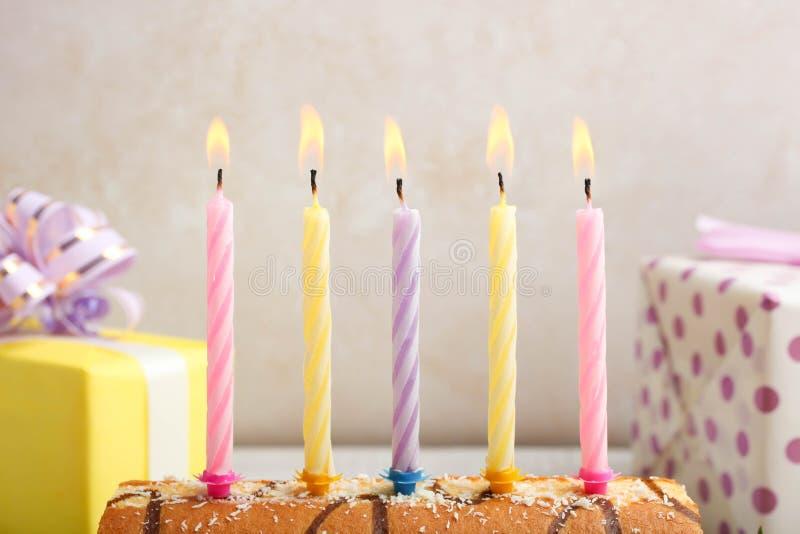 与巧克力顶部和欢乐蜡烛的小甜面包 库存图片