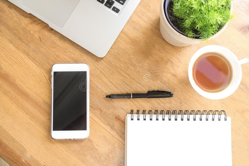 与巧妙的电话、茶,膝上型计算机、笔、植物和笔记本的办公桌木桌 与拷贝空间的顶视图 工作在家和o 免版税库存照片