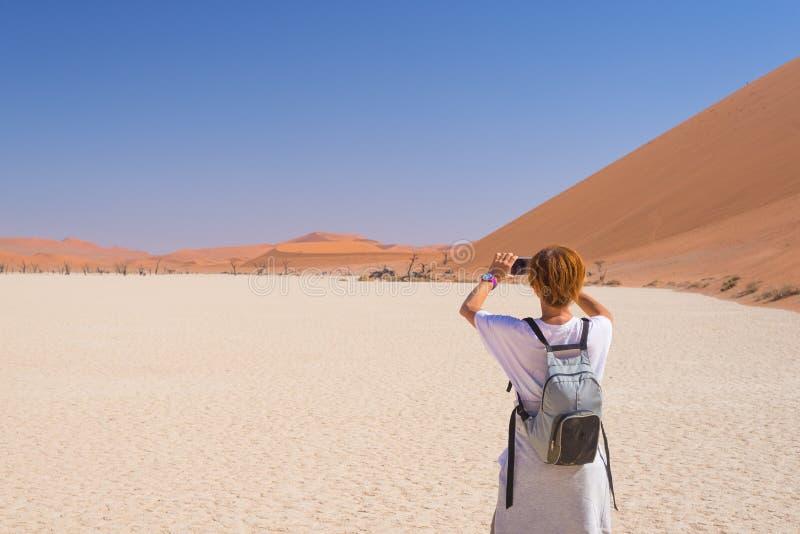 与巧妙的电话的旅游采取的照片在Sossusvlei,纳米比亚沙漠, Namib Naukluft国家公园,纳米比亚 旅行冒险和exp 免版税库存照片