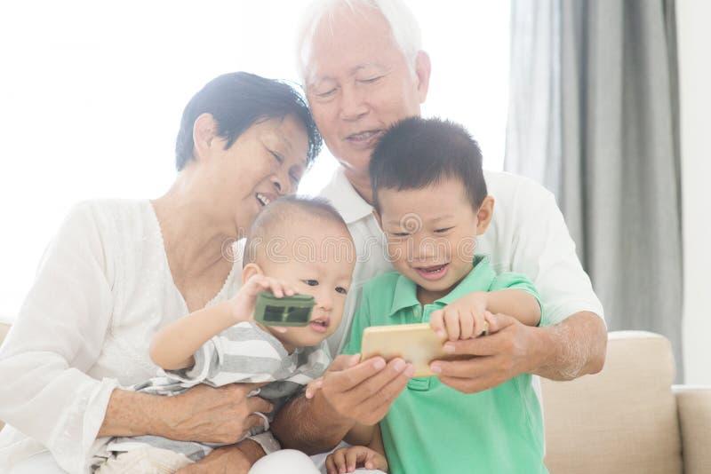 与巧妙的电话的祖父母和孙selfie 免版税库存图片