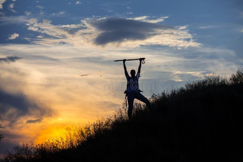 与巨型的云彩的女性远足者剪影在 库存照片