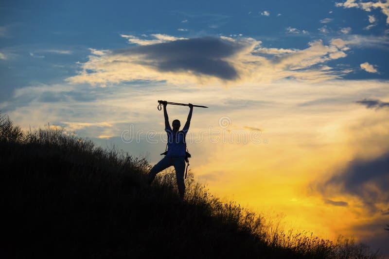与巨型的云彩的女性远足者剪影在 免版税库存图片