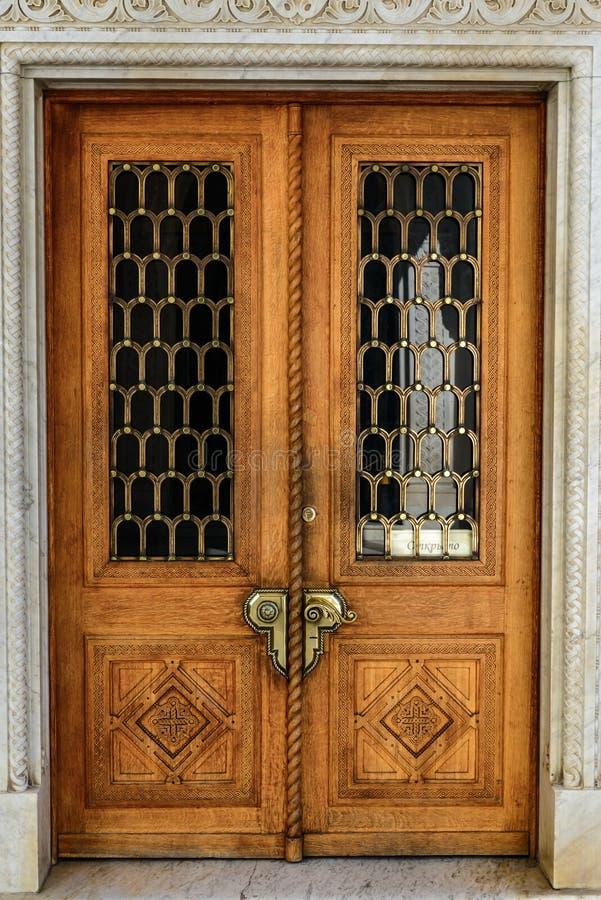与巨型的古铜色把柄的老木被雕刻的门 免版税图库摄影