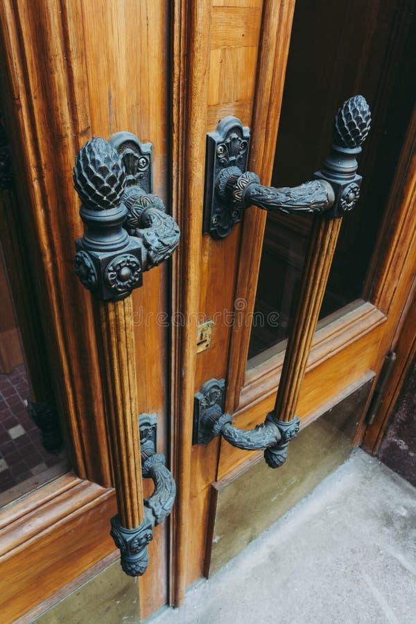 与巨型的古铜色门把手的令人惊讶的木门在艺术装饰样式 免版税库存照片